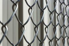 Barrière de maillon de chaîne sur un fond de bokeh d'un bâtiment en métal Image libre de droits