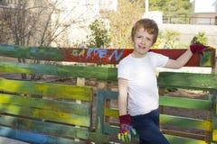 Barrière de peinture de garçon dans le jardin Photo stock