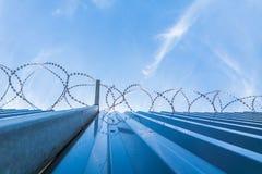Barrière de protection de Barbwire avec le ciel bleu Photographie stock libre de droits