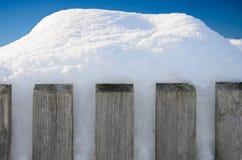 Barrière en bois avec des piles de neige devant le ciel bleu Photos libres de droits