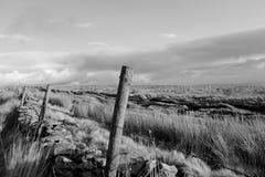 Barrière en bois de poteau et mur en pierre dans un domaine Photos stock