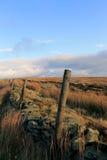 Barrière en bois de poteau et mur en pierre dans un domaine Images stock