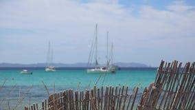 Barrière en bois et bateau de deux blancs flottant sur l'eau de mer banque de vidéos
