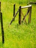 Barrière en bois et rouillée sur un vert, herbe de campagne Images stock