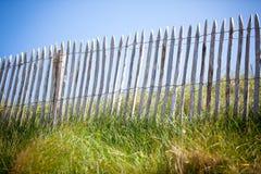 Barrière en bois, herbe verte et ciel bleu Photographie stock libre de droits