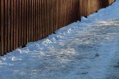Barrière en bois par la petite route neigeuse Photo stock