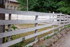 Barrière en bois rurale grise le long d'une cour vide Photographie stock libre de droits