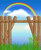 Barrière en bois sur l'herbe verte et l'arc-en-ciel Images stock