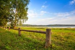 Barrière en bois sur la côte de lac, paysage russe Photographie stock libre de droits