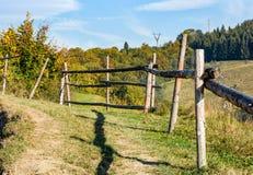 Barrière en bois sur le flanc de coteau près de la forêt photographie stock