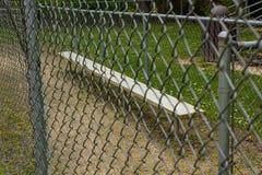 barrière et banc au terrain de base-ball au parc images stock