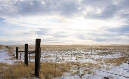 Barrière et prairie de barbelé avec les cieux nuageux ci-dessus Photo stock