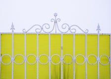Barrière figure en métal blanc sur un fond jaune Photo libre de droits