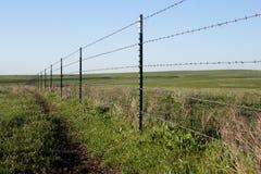 Barrière rustique à une ferme avec des brins de barbelé images stock