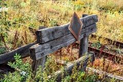 Barrière sur la voie ferrée avec l'herbe envahie photographie stock
