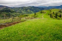 Barrière sur le pré de flanc de coteau en montagne Photographie stock