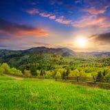 Barrière sur le pré de flanc de coteau en montagne au coucher du soleil Image stock