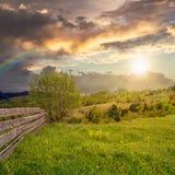 Barrière sur le pré de flanc de coteau en montagne au coucher du soleil Photo libre de droits