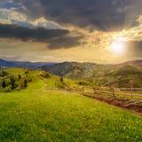 Barrière sur le pré de flanc de coteau en montagne au coucher du soleil Photo stock