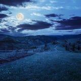 Barrière sur le pré de flanc de coteau en montagne la nuit Photo stock