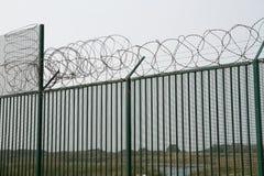 Barrière verte avec le fil de rasoir gardant le terminal du ferry français Images stock