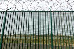 Barrière verte avec le fil de rasoir gardant le terminal du ferry français Photographie stock libre de droits