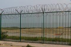 Barrière verte avec le fil de rasoir gardant le terminal du ferry français Image stock