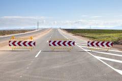 Barrières de route sur une nouvelle route Photographie stock libre de droits