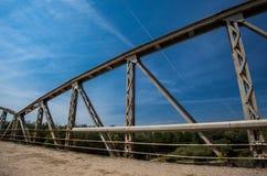 Barrières rouillées en métal sur le pont Route avec l'asphalte criqué images stock