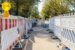 Barricadas rojas y blancas con los pilotos en una calle en un re fotos de archivo libres de regalías