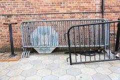 Barricadas viejas del metal almacenadas al lado del edificio de ladrillo foto de archivo libre de regalías