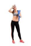 Barrido cansado joven de la mujer de la aptitud sudado de la frente con la botella de agua fresca Foto de archivo