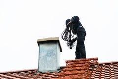 Barrido de chimenea en el tejado del trabajo doméstico Foto de archivo