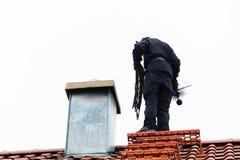 Barrido de chimenea en el tejado del trabajo doméstico Foto de archivo libre de regalías
