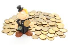 Barrido de chimenea en una pila de monedas. Aislado en blanco Fotos de archivo libres de regalías