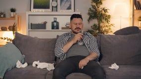 Barrido gritador de consumición del alcohol del individuo triste con el tejido que se sienta en el sofá que ve la TV almacen de metraje de vídeo