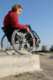 Barrier. Handicapped woman on wheelchair going down the high concrete kerb stock photos