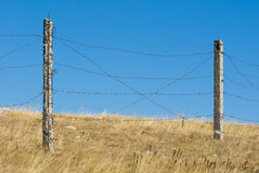 Barrier with barbed wire against blue sky Stock Images