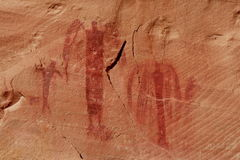 Barrier Canyon Pictographs. Three ancient Barrier Canyon style pictograph figures appearing angel like on red sandstone cliff in desert southwest Stock Photo