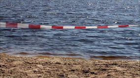Barrier caution tape on bathing lake, no continuity. Forbidden, Barrier caution tape on bathing lake, no continuity stock footage