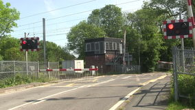 Barrier coming down at a level crossing. Red flashing warning lights just before the barrier comes down at a level crossing on the main London to Scotland stock video footage