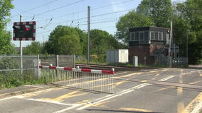 Barrier coming down at a level crossing. Red flashing warning lights just before the barrier comes down at a level crossing on the main London to Scotland stock footage