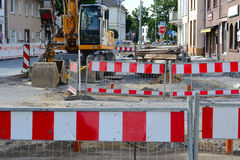 Barrier with excavator. Red and white Barriers in the downtown Royalty Free Stock Photography