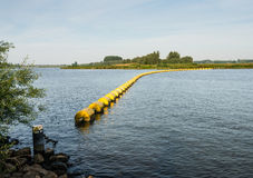 Barrier of floating switched yellow objects. Wide creek in a Dutch nature reserve closed with a barrier of floating switched yellow plastic objects Stock Images