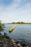 Barrier of floating switched yellow objects. Wide creek in a Dutch nature reserve closed with a barrier of floating switched yellow plastic objects Royalty Free Stock Photo