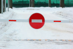 Barrier with no entry sign on snowy road Royalty Free Stock Photos