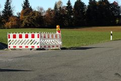 Barrier on a road. With autumn landscape in background Royalty Free Stock Image