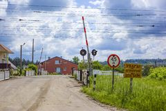 Barriera ferroviaria aperta con i segnali stradali dentro un piccolo villaggio in Ucraina fotografie stock