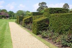 Barriera scolpita e un percorso della ghiaia al giardino del castello di Hever in Inghilterra Immagini Stock Libere da Diritti