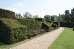 Barriera scolpita e un percorso della ghiaia al giardino del castello di Hever in Inghilterra Fotografia Stock